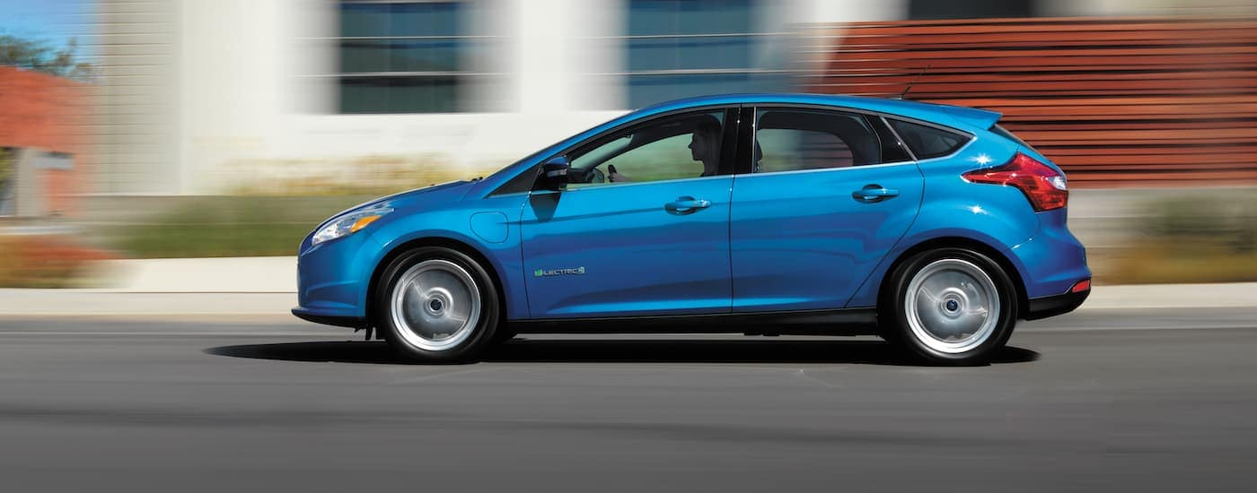 A blue 2017 Ford Focus Electric is driving past a white house, shown from the side.