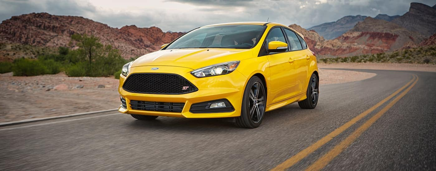 A yellow 2017 Ford Focus ST is driving past red rock hills.