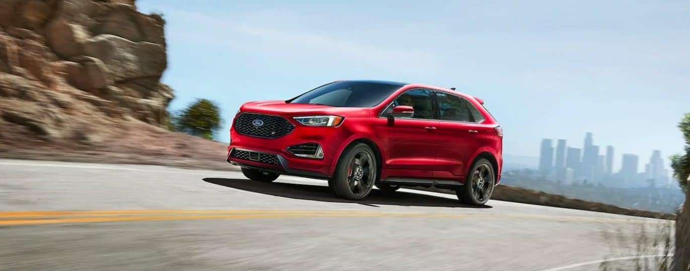 A red 2021 Ford Edge ST is shown driving down a road with a city in the distance.
