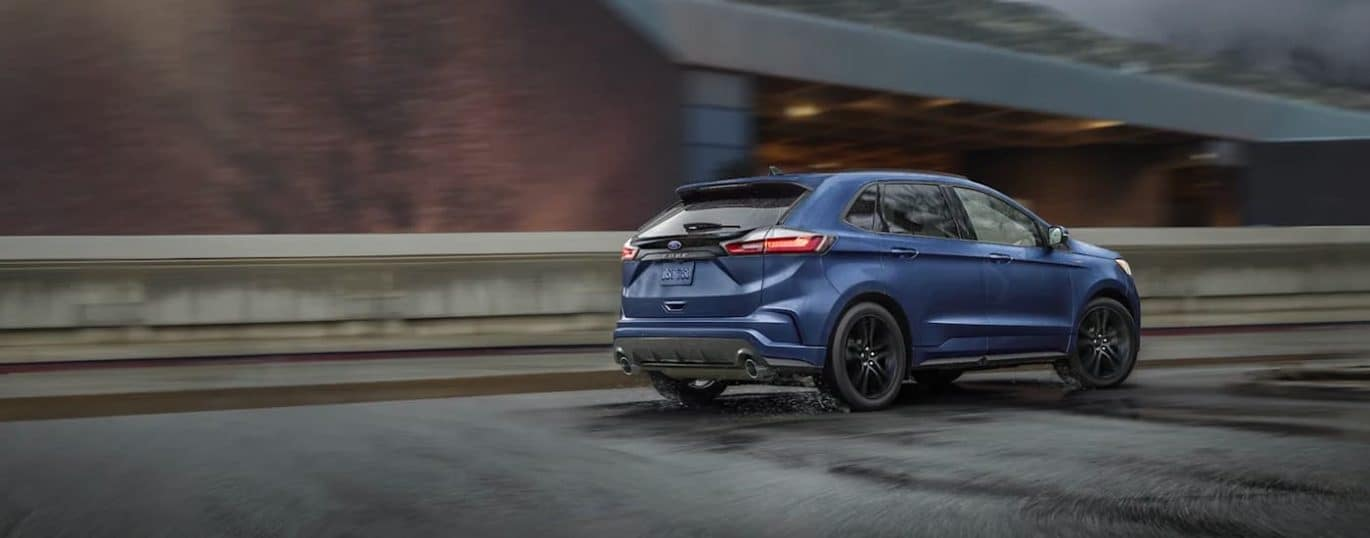 A blue 2021 Ford Edge ST is shown from the rear while driving down a road in the rain.