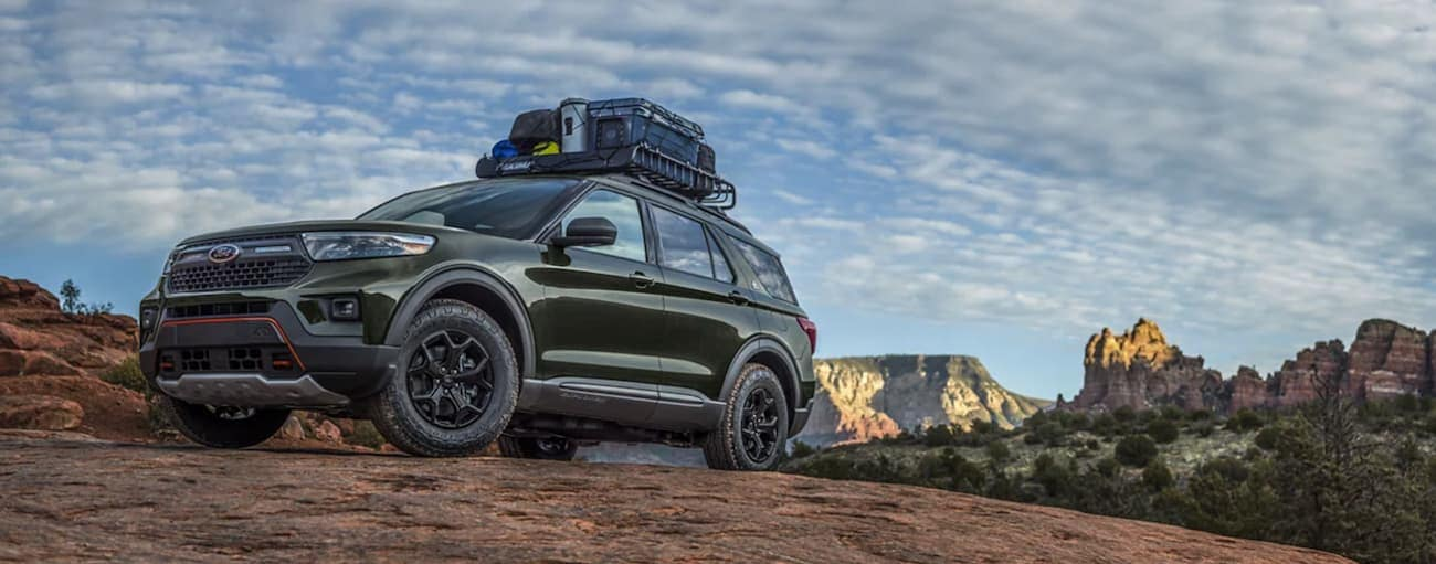 A green 2021 Ford Explorer Timberline edition is off-roading in the desert with gear on the roof.