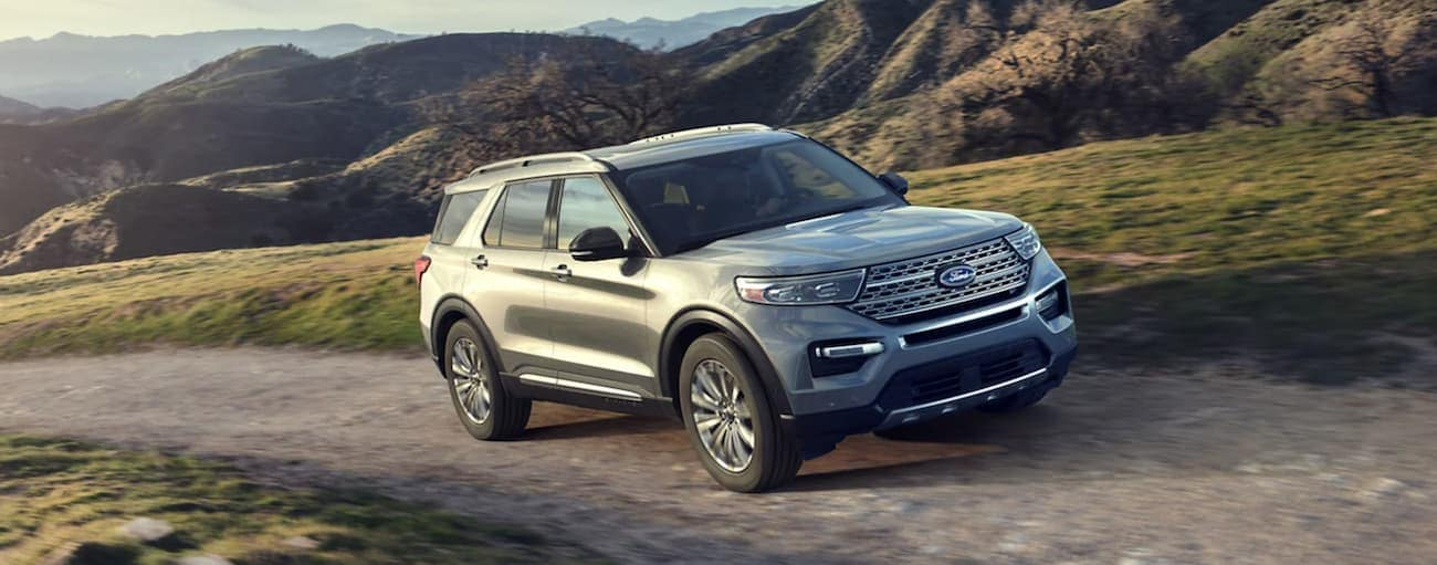 A silver 2021 Ford Explorer is driving on a dirt path past mountains after winning the 2021 Ford Explorer vs 2021 Kia Telluride comparison.