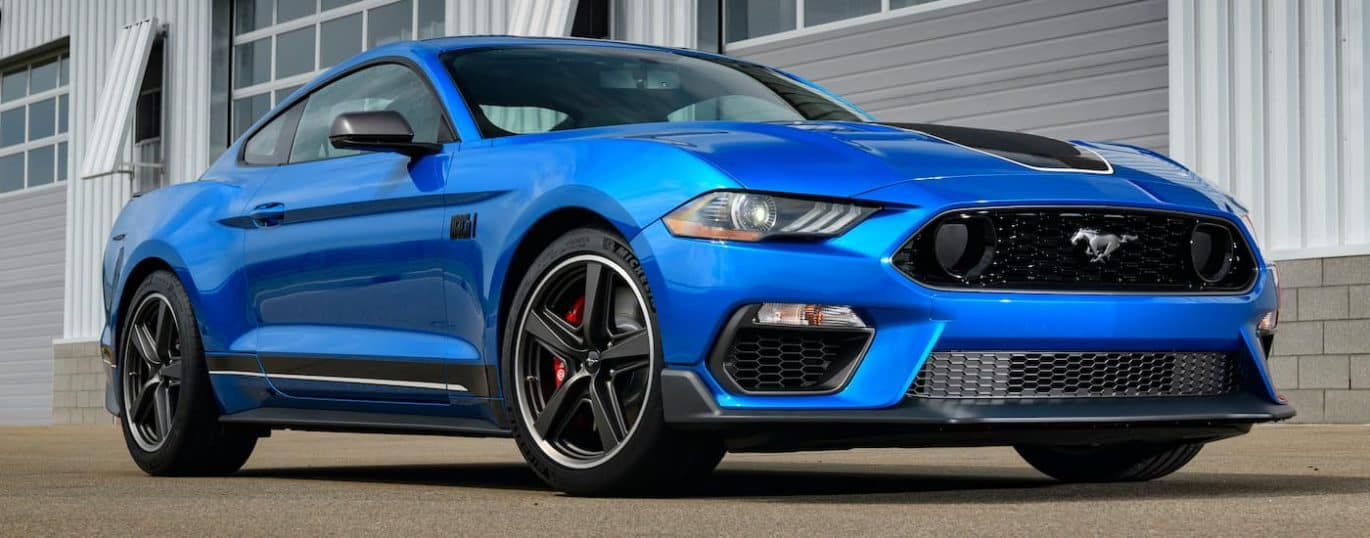 A blue 2021 Ford Mustang Mach 1 is shown from the side parked in front of a garage.