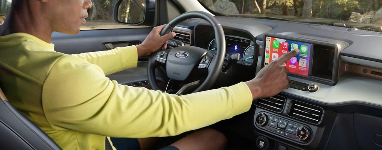 The interior of a 2022 Ford Maverick shows a man sitting in the drivers seat adjusting the infotainment screen.