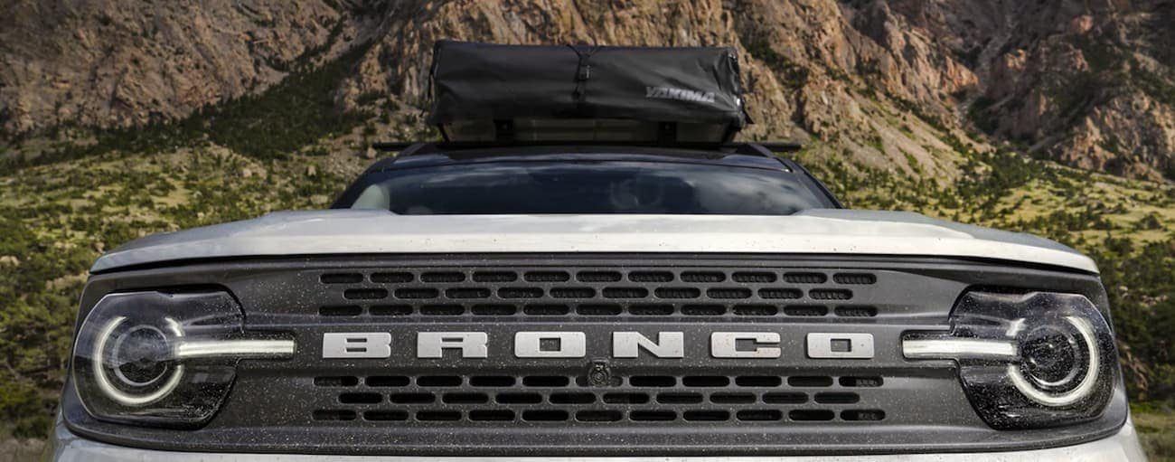 The front grille of a white 2021 Ford Bronco Sport is shown from a low angle.