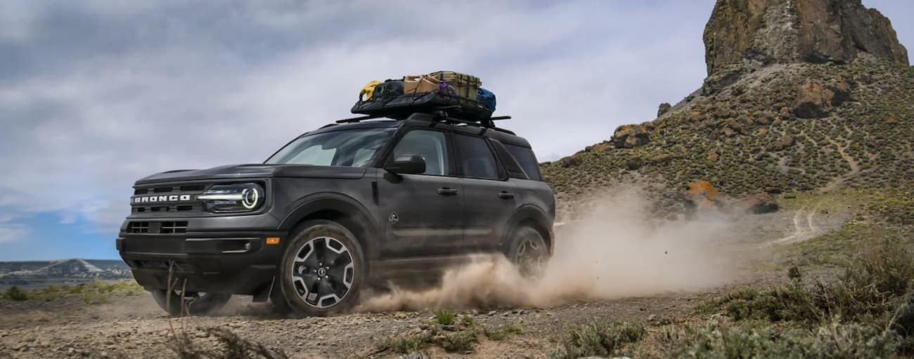 A grey 2021 Ford Bronco Sport is shown off-roading in the desert during a 2021 Ford Bronco Sport vs 2021 Subaru Crosstrek comparison.