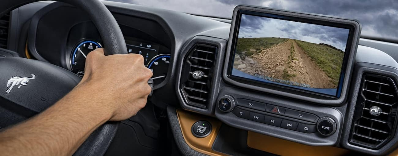 The interior of a 2021 Ford Bronco Sport shows the steering wheel and infotainment screen.
