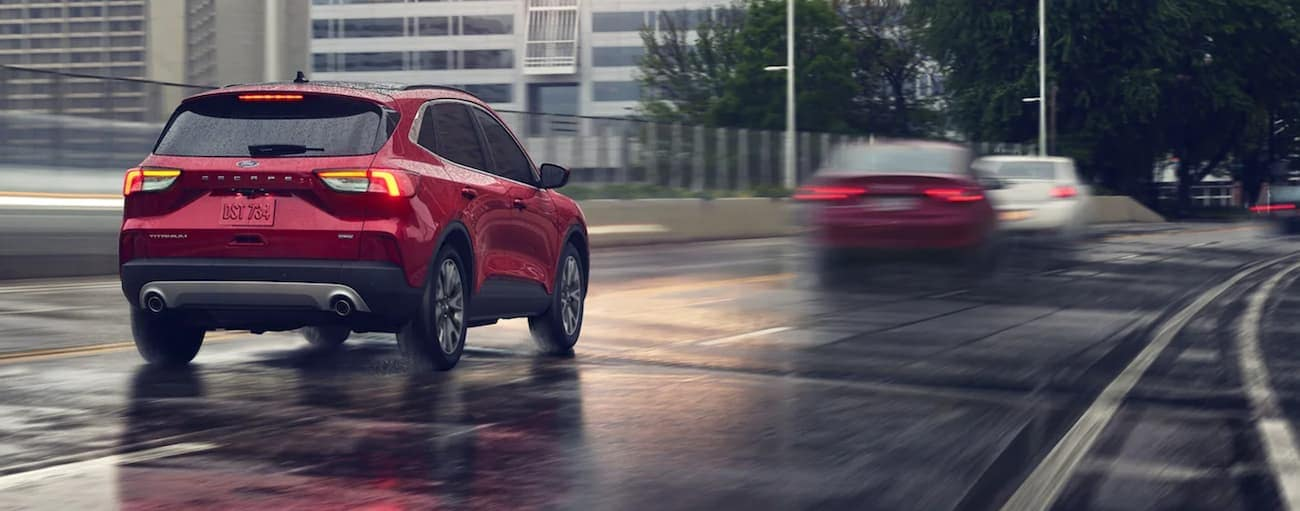 A red 2021 Ford Escape is driving on a rainy highway road.