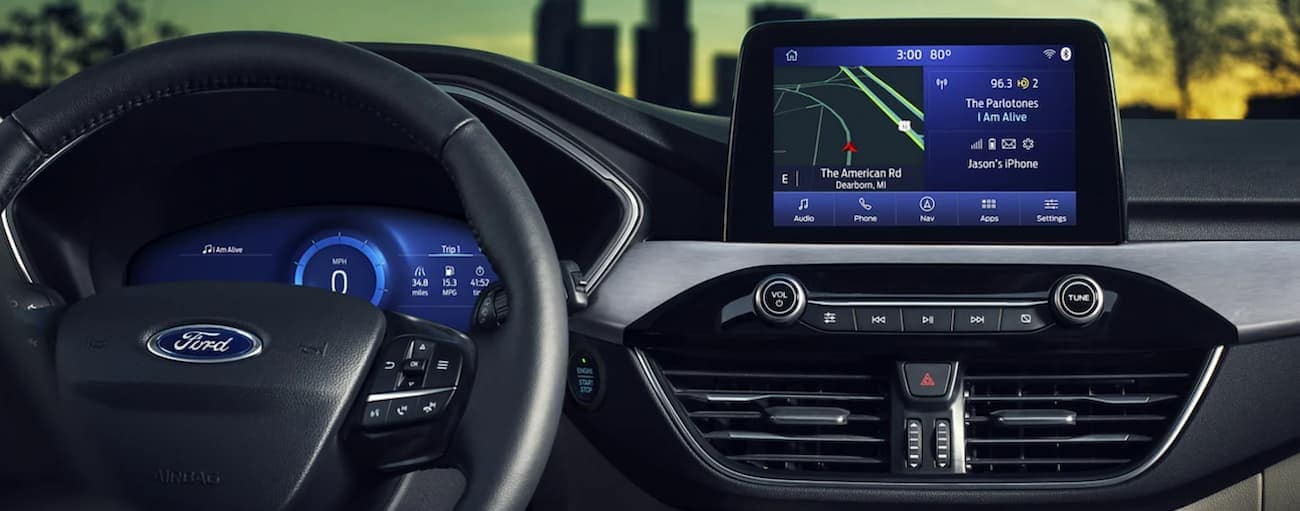 The interior of a 2021 Ford Escape shows the steering wheel and infotainment screen.