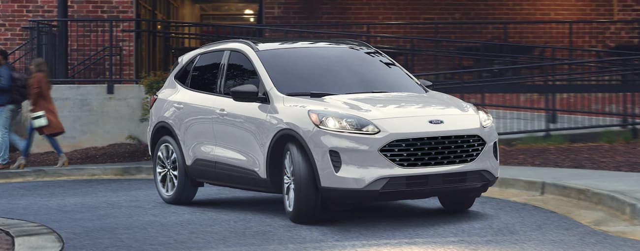 A white 2021 Ford Escape is driving on a one way road during a 2021 Ford Escape vs 2021 Chevy Equinox comparison.