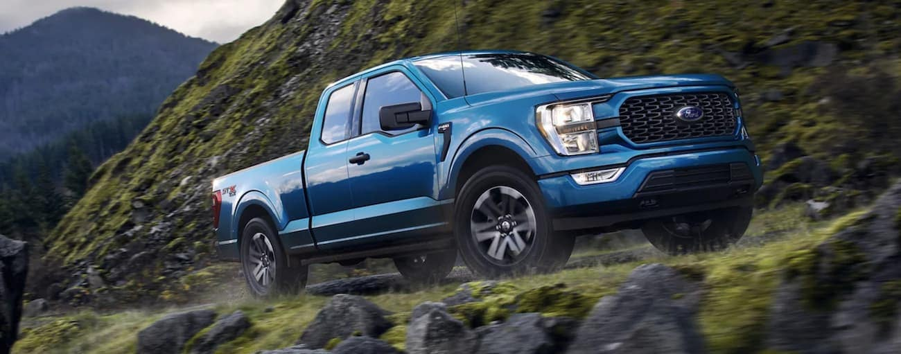 A blue 2021 Ford-150 is shown driving in the mountains after winning a 2021 Ford F-150 vs 2021 Toyota Tundra comparison.