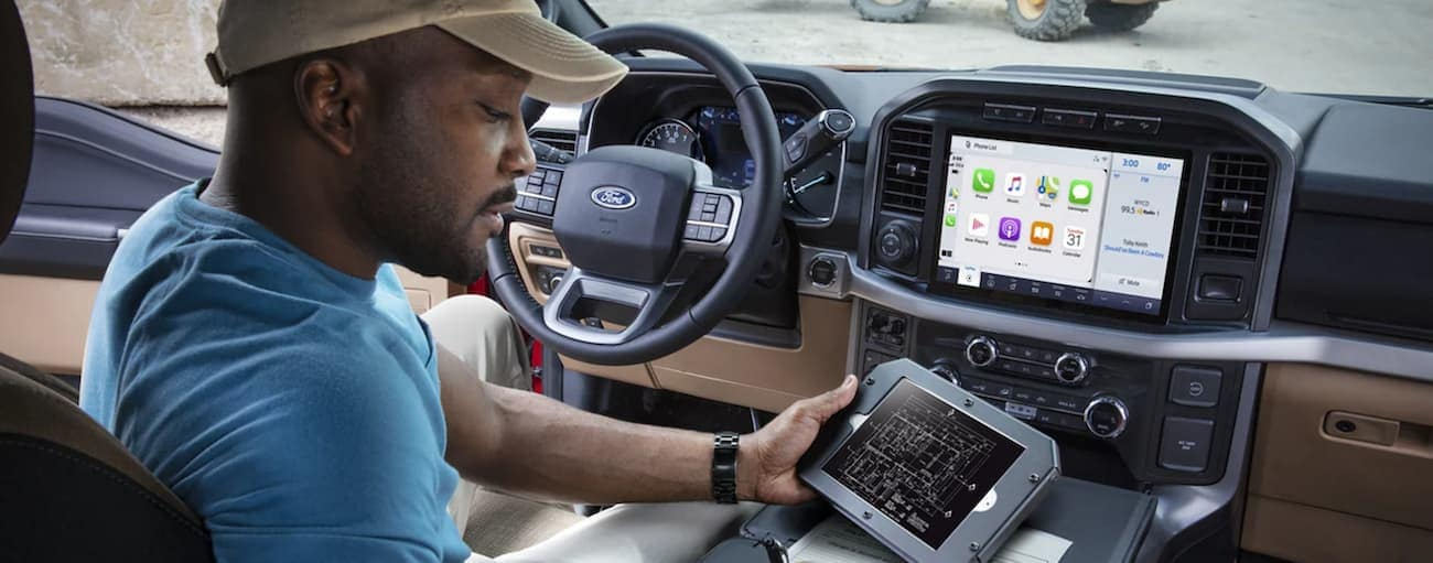 The interior of a 2021 Ford F-150 shows a man using a tablet in the front seat.