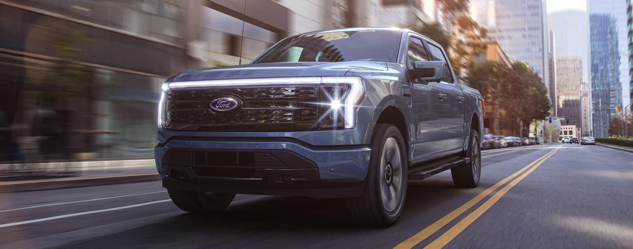 A blue 2022 Ford F-150 Lightning is shown driving down a city street.