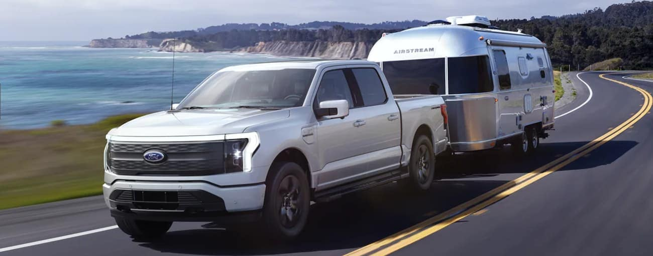 A silver 2022 Ford F-150 Lightning is towing a trailer on a road next to the ocean.