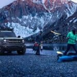 A grey 2021 Ford Bronco is shown on a shore in the mountains next to people going kayaking.