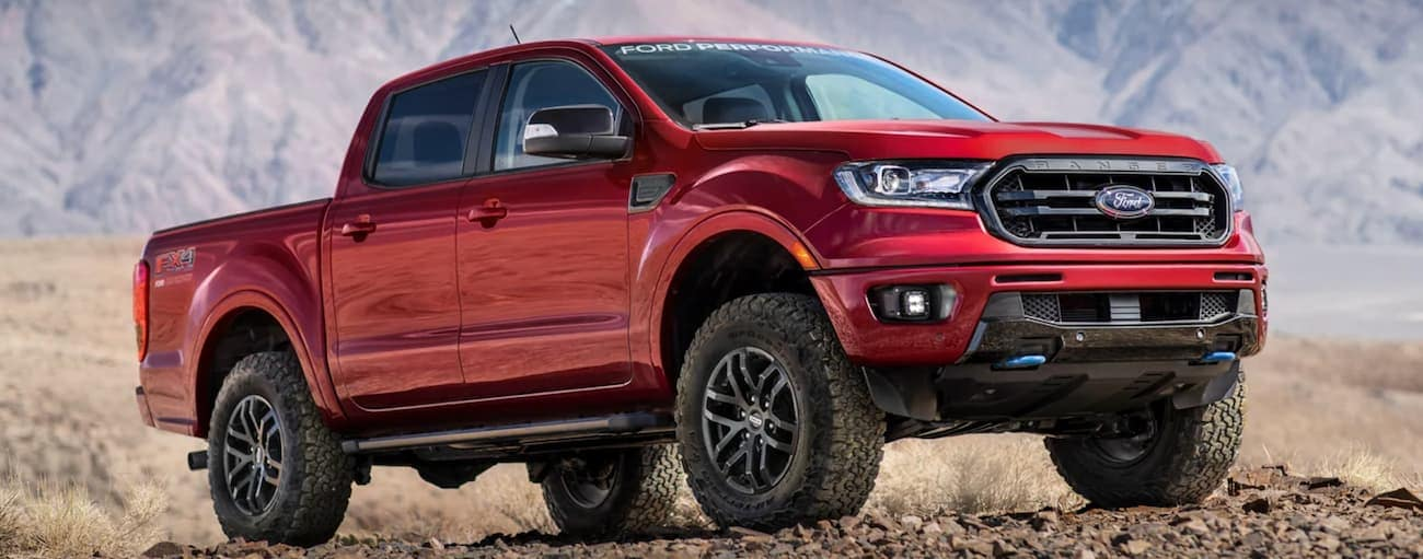A red 2021 Ford Ranger is parked in a desert during a 2021 Ford Ranger vs 2021 Toyota Tacoma comparison.