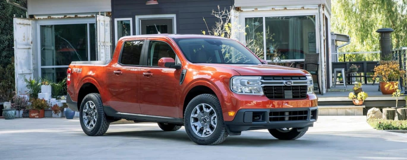 A red 2022 Ford Maverick Lariat is shown parked in a driveway.