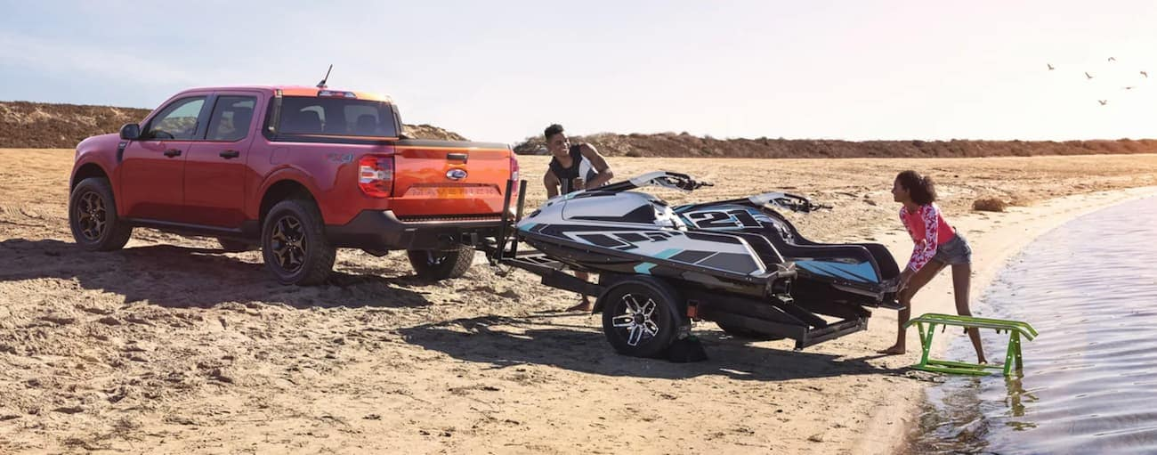 An orange 2022 Ford Maverick is towing a jet-ski on a beach after winning a 2022 Ford Maverick VS 2022 Hyundai Santa Cruz comparison.