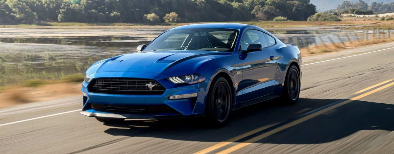 A blue 2021 Ford Mustang High Performance is shown driving past a lake after winning a 2021 Ford Mustang vs 2021 Chevy Camaro comparison.