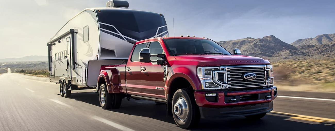 A red 2022 Ford Super Duty is towing a camper on an open highway.