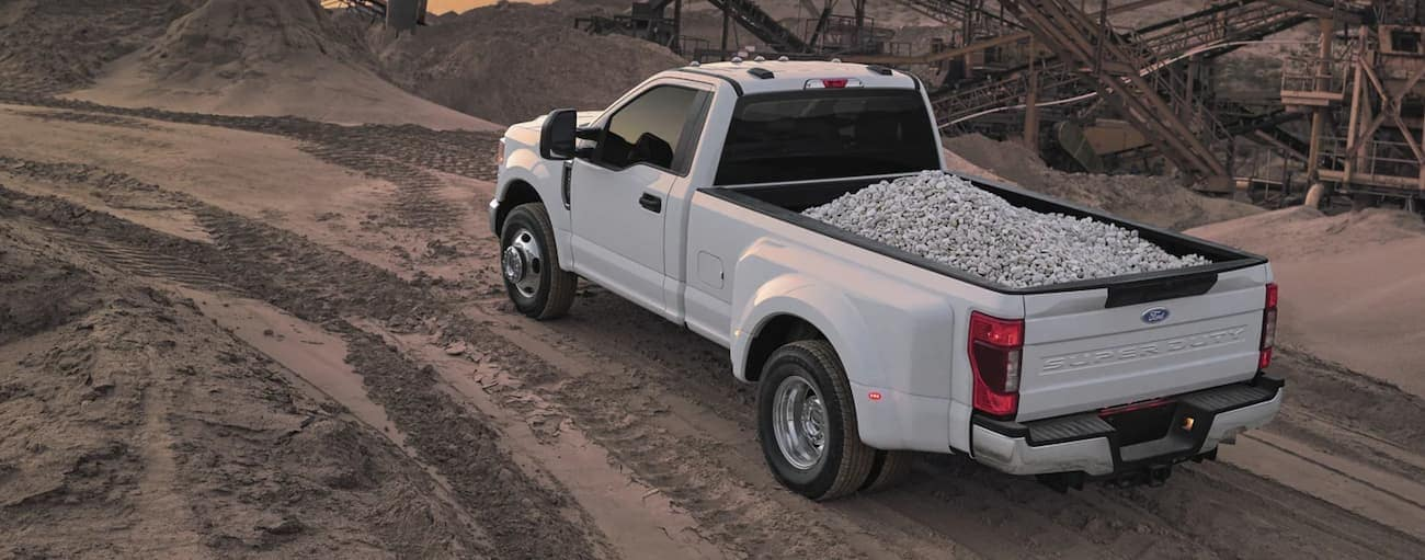 A white 2022 Ford Super Duty is using the bed to transport crushed stone.