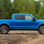 A blue 2019 Ford F-150 is shown from the side parked in a dirt field surrounded by forest.