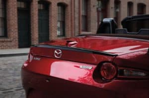 Closeup shot of a stylish red 2019 Mazda MX-5 Miata car with the convertible top down parked across from brick buildings