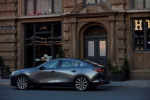 Stylish gray 2019 Mazda3 sedan car parked in front of a city building during the day