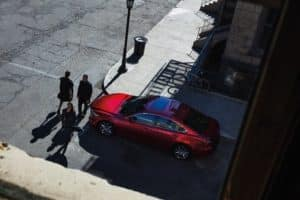 Arial view of a red Mazda6 stopped at an intersection while three pedestrians walk in front of the sedan