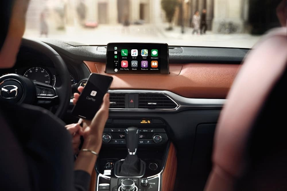 Two-tone brown and black interior of a 2019 Mazda CX-9 showcasing the MAZDA CONNECT infotainment center with Apple CarPlay for iPhone and a woman holding a black iPhone®