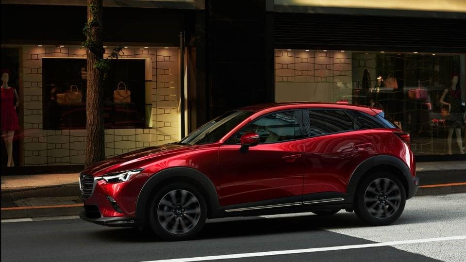red 2020 Mazda CX-3 driving down a paved city street past a store with women's clothing and accessories in the window
