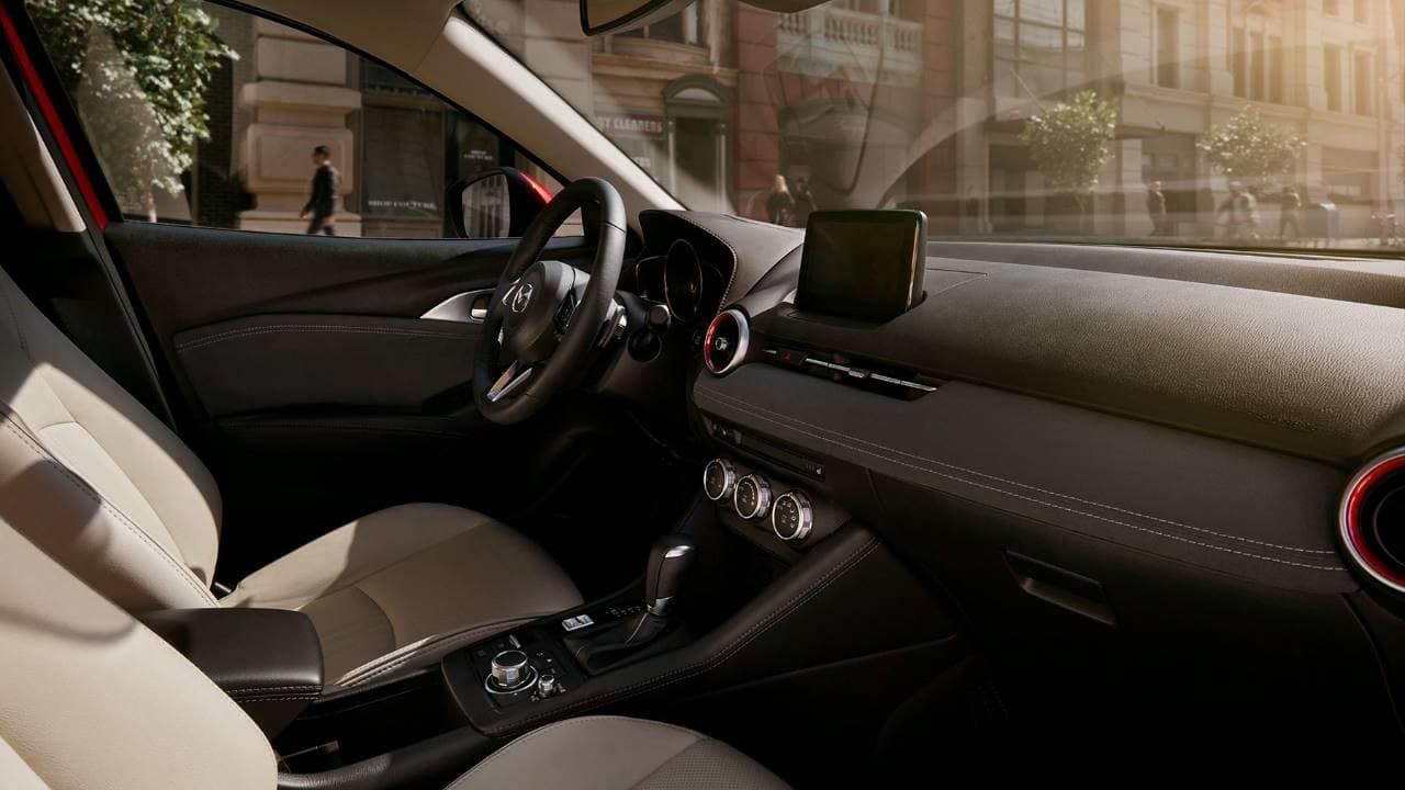 interior of a 2020 Mazda CX-3 with two-tone black and cream-colored upholstery and chrome accents