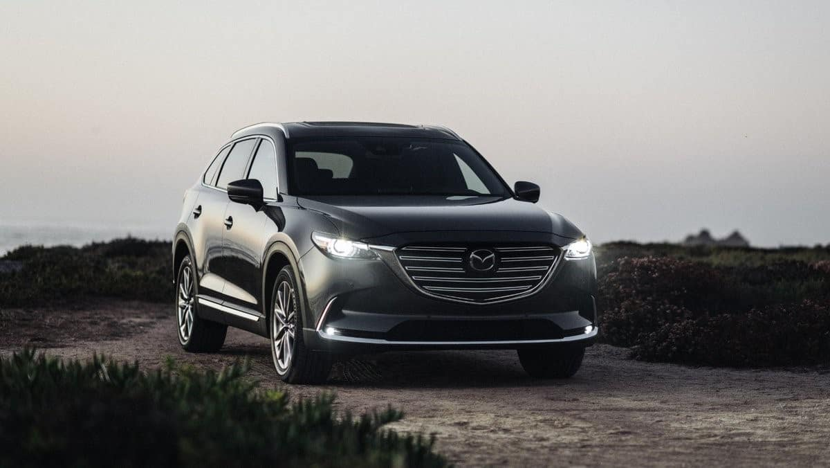 black 2020 Mazda CX-9 parked on a dirt path with the headlights illuminated
