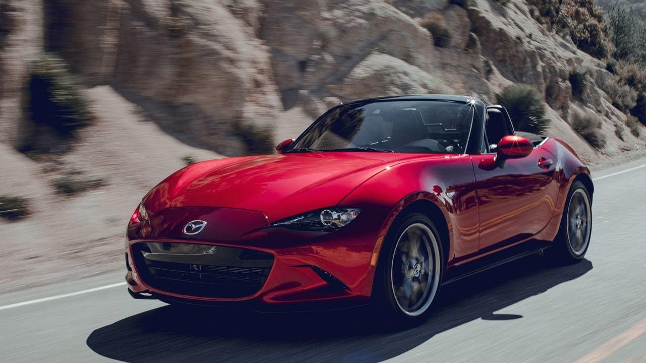 red 2020 Mazda MX-5 soft top convertible driving quickly by a mountain side with the top down