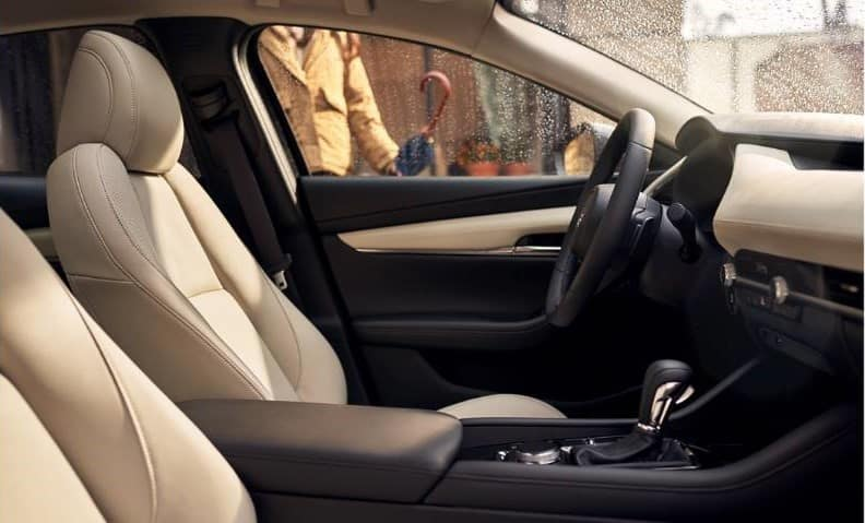 vehicle interior of a 2020 Mazda3 car with cream-colored leather with black leather and chrome accents in the cabin