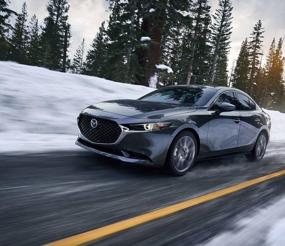 black 2020 Mazda3 sedan AWD compact car driving quickly on a snowy road in slick weather conditions during winter