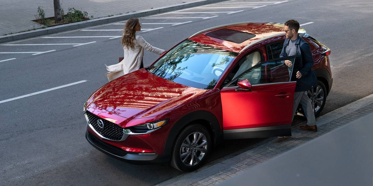 red 2020 Mazda CX-30 parked on a city street next to shops and pedestrians
