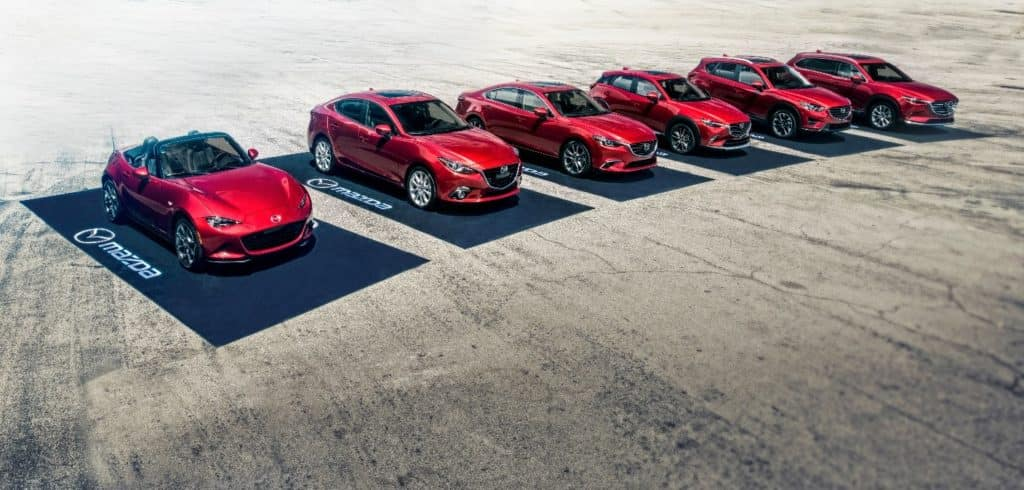 six new red 2020 Mazda cars and SUVs parked on black Mazda-branded car mats on sandy pavement represent the automakers newest lineup for the year
