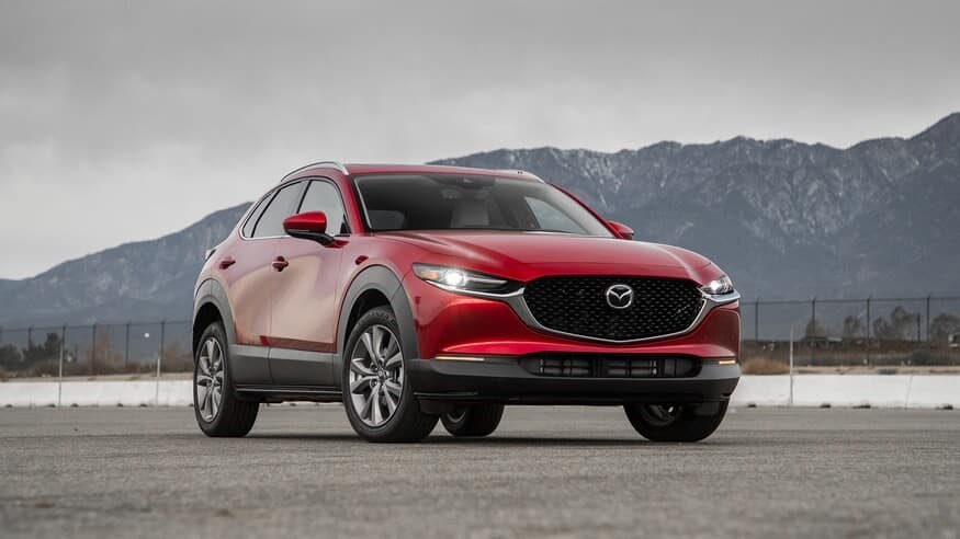 red 2020 Mazda-CX30 parked in an empty parking lot with LED daytime running lights turned on in front of mountains under a gray sky