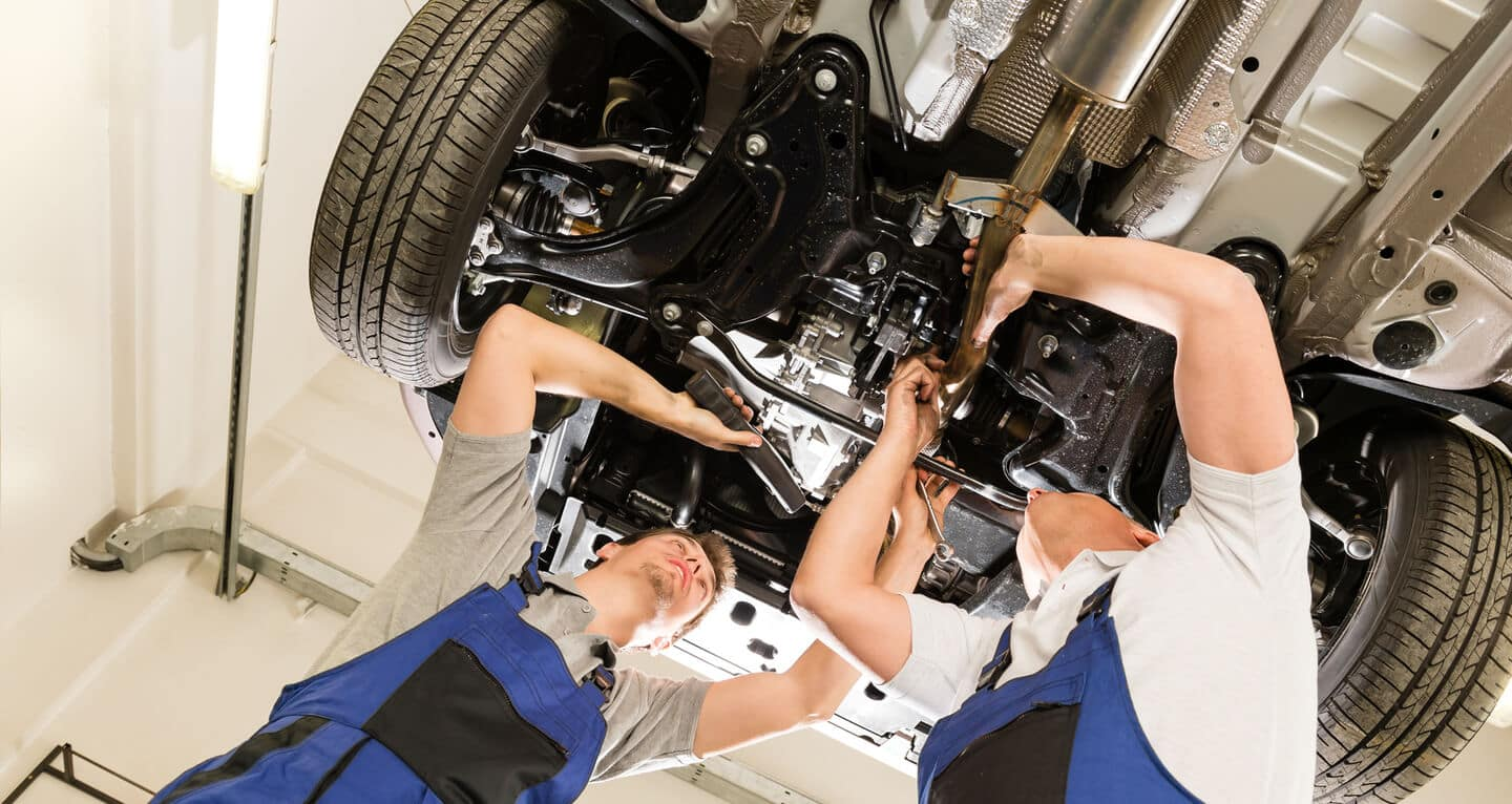 Two mechanics under car in service center