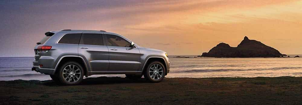 2018 Jeep Grand Cherokee parked in front of coean at sunset