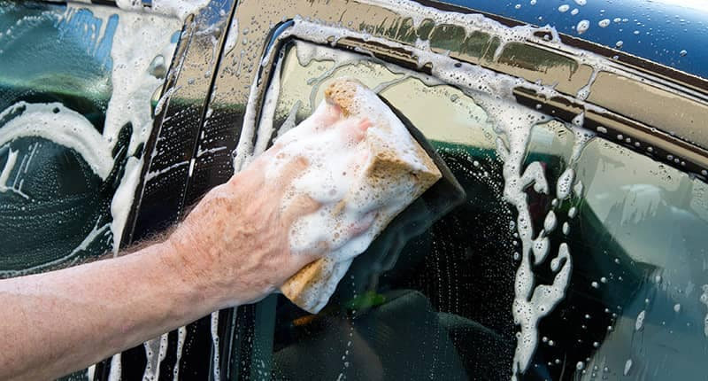 Close up of hand washing a car