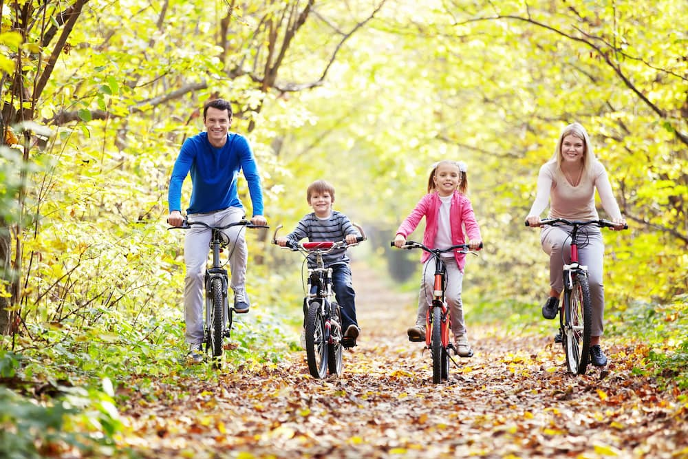 Family of 4 biking on a wooded path