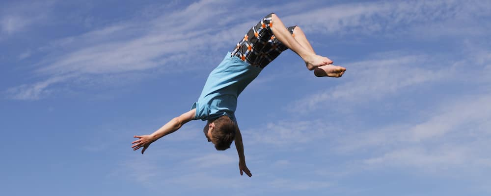 Young boy doing a backflip on a trampoline