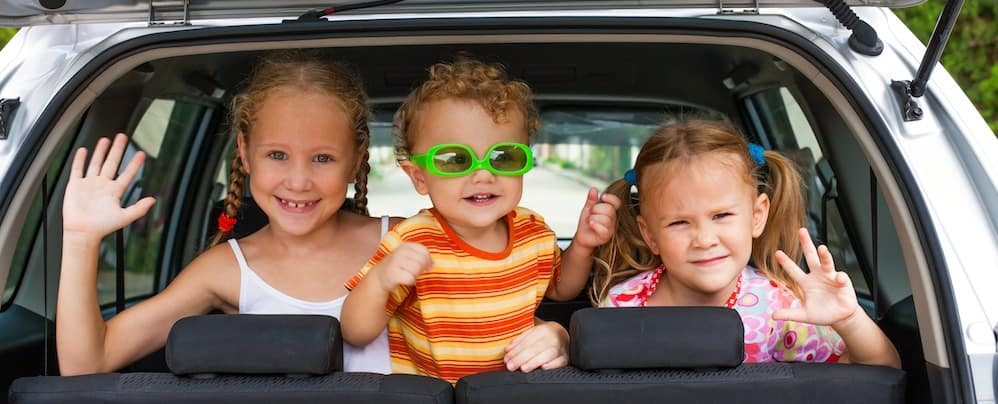 Two little girls and one little boy wearing green sunglasses smiling and looking out the back of a car