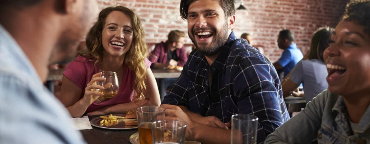 friends eating at bar restaurant_140442326