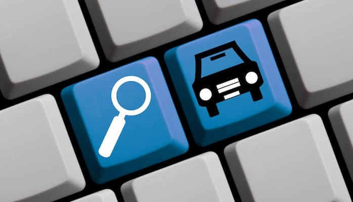 Computer keys with magnifying glass and automobile icons on them