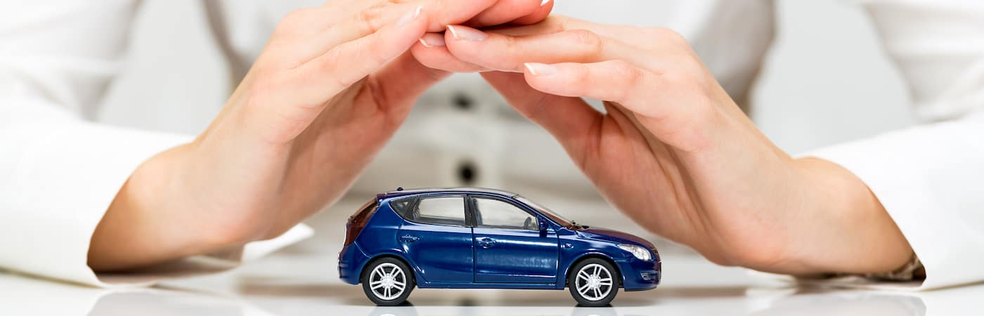 Hands covering toy car