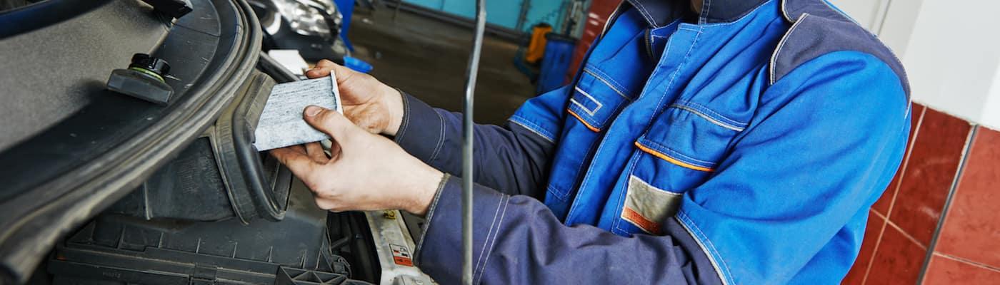Technician replacing engine air filter
