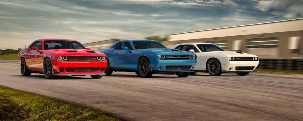 Trio of Dodge Challengers racing each other on a open track